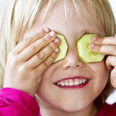 Portrait of little girl with two slices of cucumber on her eyes